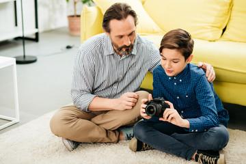 Man looking at his son holding new camera