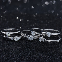 Silver engagement rings with diamonds on black background with bokeh