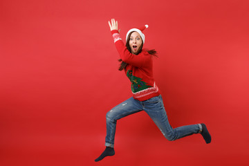 Amazed Santa girl in Christmas hat jumping, rising hands spreading legs, keeping mouth wide open isolated on red background. Happy New Year 2019 celebration holiday party concept. Mock up copy space.