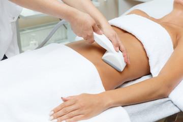 Cosmetologist performs vacuum roller massage LPG of abdomen  in the beauty salon