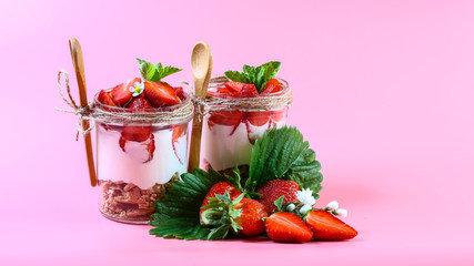 dessert with fresh strawberry, cream cheese and strawberry jam on glasses. Isolated on pink background, copy space