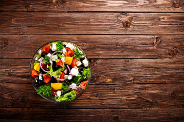 Dieting healthy salad on rustic wooden table top view