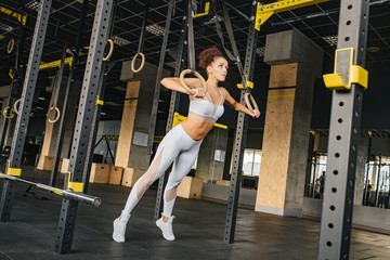 Fitness sports girl wearing in white top and leggings exercising on gymnastic rings in gym. Sport and health. Fitness life.