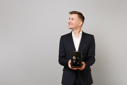 Smiling young business man in classic suit looking aside and holding metal bank safe for money accumulation isolated on grey background. Achievement career wealth business concept. Mock up copy space.