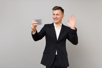 Young business man waving, greeting with hand, doing taking selfie shot on mobile phone, making video call isolated on grey background. Achievement career wealth business concept. Mock up copy space.