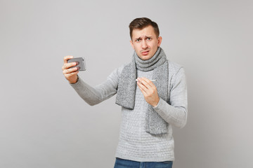 Puzzled young man in gray sweater, scarf holding thermometer, doing selfie shot on mobile phone, making video call isolated on grey background. Health, ill sick disease treatment, cold season concept.