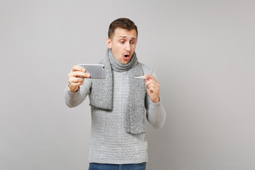 Shocked young man in gray sweater, scarf holding thermometer, doing selfie shot on mobile phone, making video call isolated on grey background. Health ill sick disease treatment, cold season concept.