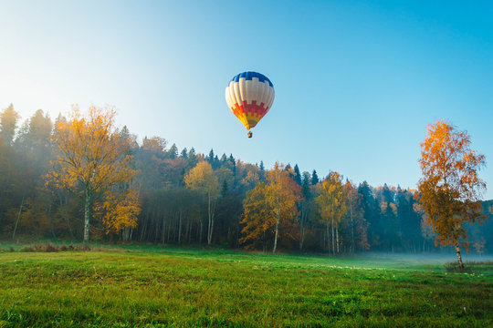 Colorful hot air balloon over the green field. Outdoor activity over national park. Traveling concept.
