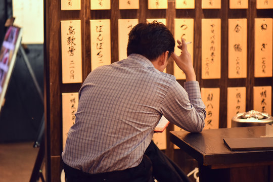 Rear view of man sitting with cigarette in restaurant