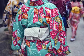 Rear view of women in kimono walking outdoors