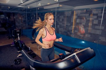 Woman running on treadmill. Gym interior, healthy lifestyle concept.