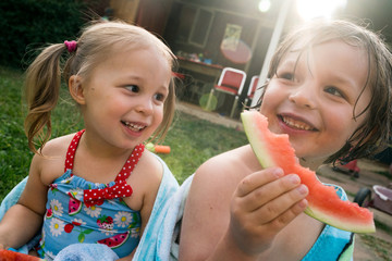 Smiling girl and boy eating watermelon slices outdoors