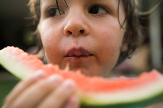 Close up of boy eating a watermelon slice