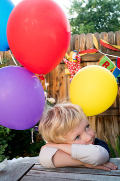 Thoughtful boy leaning on table with balloons