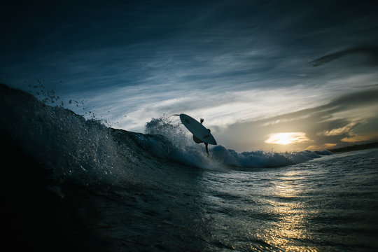 Surfer surfing in sea during sunset
