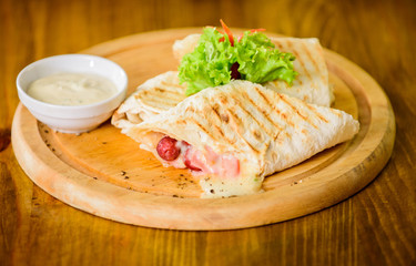Lavash burrito stuffed meat sausage and cheese sauce served salad. Meat wrapped with lavash burrito. Restaurant meal traditional cuisine. Burrito tortilla served wooden board. Restaurant food concept