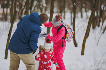 Young family man woman, little girl in winter warm clothes playing, making snowman in snowy park or forest outdoors. Winter fun, leisure on holidays. Love relationship family people lifestyle concept.