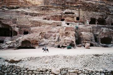 Man riding horse on desert landscape