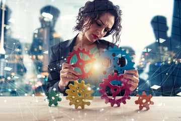 Businesswoman tries to connect gears pieces. Concept of Teamwork, partnership and integration. double exposure