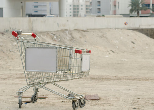 An abandoned metal shopping trolly cart in dusty dubai, discarded and left in the sparse desert dust. Abandoned in dubai.