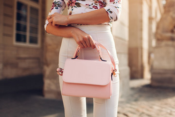 Close-up of stylish female handbag. Young woman wearing beautiful outfit and accessories outdoors. City fashion