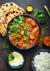 Wall Mural - Traditional Indian dish Chicken tikka masala with spicy curry meat in bowl, basmati rice, bread naan, yoghurt raita sauce on rustic dark background, top view, close up. Indian style dinner from above