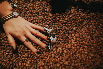 Female hand touching coffee beans