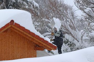 Ein Mann räumt schweren Schnee von einem Hausdach. Gefährliches Gewicht auf einem Dach