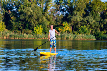 Happy man is training on a SUP board
