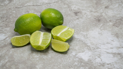two ripe green limes with juicy lime sections and wedges on a gray marble kitchen counter with copy space