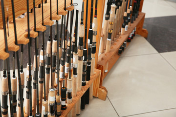 Stand with different fishing rods in sports shop, closeup