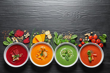 Various soups, ingredients and space for text on wooden background, flat lay. Healthy food