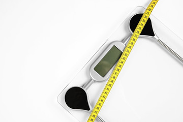 Modern scales and tape measure isolated on white, top view