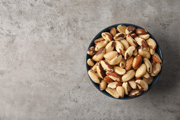 Bowl with tasty Brazil nuts and space for text on grey background, top view