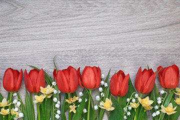 Bunch of red tulips, daffodils and lily of the valley flowers on light wooden background