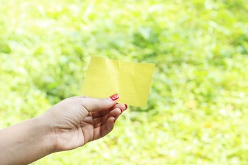 Hand hold yellow blank torn paper on green