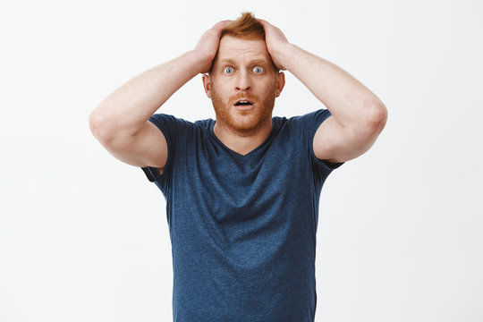 What should I do now. Portrait of shocked and desperate attractive redhead with bristle, holding hands on hair, popping eyes and dropping jaw from shock and despair, standing over gray background