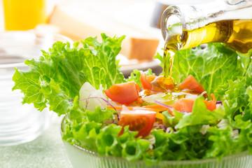 サラダにオリーブオイルをかける