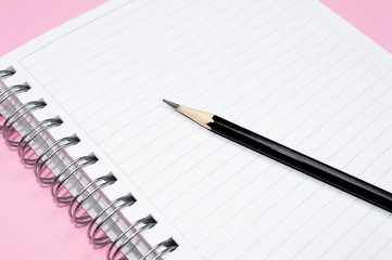 Working space: notepad and black pencil on pink background. Minimalist composition.