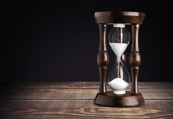 Sand running in hourglass on light background