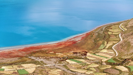 High angle view of holy Yamdrok Lake and colorful farm land, amazing blue water surface with little ripples, zigzag road cross the farm land along the mountains. Idyllic peaceful world.
