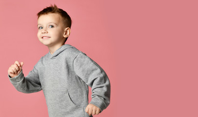 Young baby boy kid in grey hoodie with free text copy space running happy smiling on pink