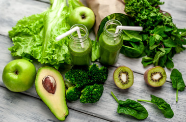 smoothie with vegetables, avocado, apple, kiwi on a wooden background. sports nutrition