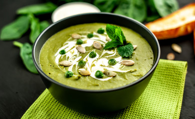 Green cream soup of spinach and broccoli. concrete or slate background. The concept of a healthy diet and diet.