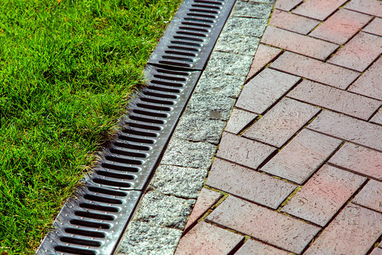 iron drainage net between paving slab and green lawn.