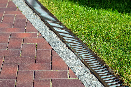 Drainage system with iron mesh along the pedestrian sidewalk with red tiles and green lawn, close-up of iron rainfall.