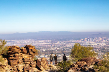 Mountain Hikers Overlooking Phoenix City Skyline