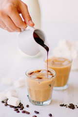 Cold coffee with milk and chocolate. Light background. Iced coffee. Concept of a cooling drink. Marshmelow and coffee beans on the table. Summer drink.