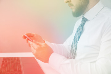 Light background. Financial business. Holding smartphone in hand. Office work with a laptop. Young bearded businessman. Light background.