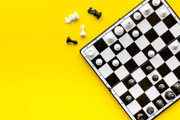 Chess game concept. Chess board with figures on yellow background top view copy space